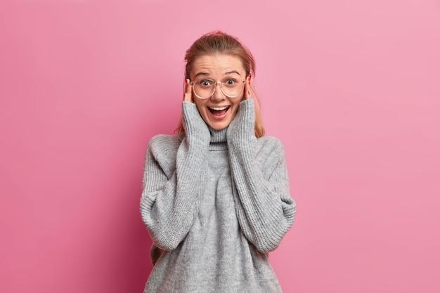 Retrato de uma garota muito alegre usando grandes óculos ópticos e um macacão enorme, rindo positivamente, assistindo a um programa engraçado