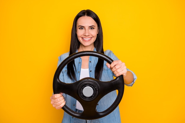Retrato de uma garota muito charmosa e alegre girando o volante