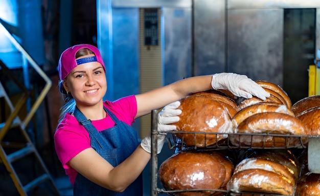 Retrato de uma garota padeiro no contexto das prateleiras com pão fresco em uma padaria. produção de pão industrial