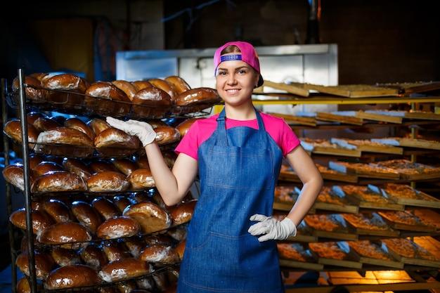 Retrato de uma garota padeiro no fundo das prateleiras com pão fresco em uma padaria. produção de pão