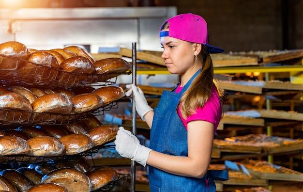 Retrato de uma garota padeiro perto de prateleiras com pão. plano de fundo de uma linha em uma padaria. produção de pão industrial