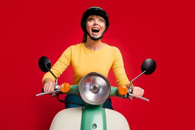 Retrato de uma garota positiva dirigindo um ciclomotor com a boca aberta na parede vermelha