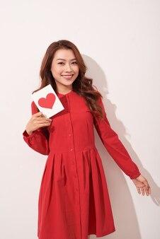Retrato de uma garota romântica feliz com um cartão postal de papel vermelho em forma de coração, desejos românticos, celebração do dia dos namorados, conceito de amor