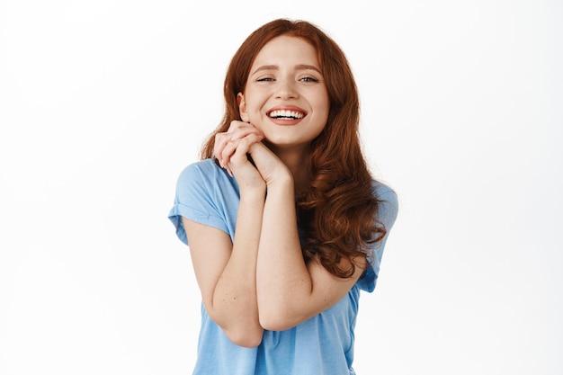 Retrato de uma garota ruiva adolescente feliz, cabeça magra nas mãos e sorrindo adorável, olhando para algo lindo e adorável, contemplando, em pé no branco.