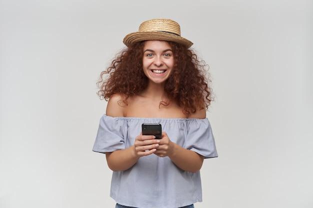 Retrato de uma garota ruiva atraente e adulta com cabelo encaracolado. usando blusa listrada de ombros largos e chapéu. segurando um telefone inteligente e um sorriso. isolado sobre a parede branca