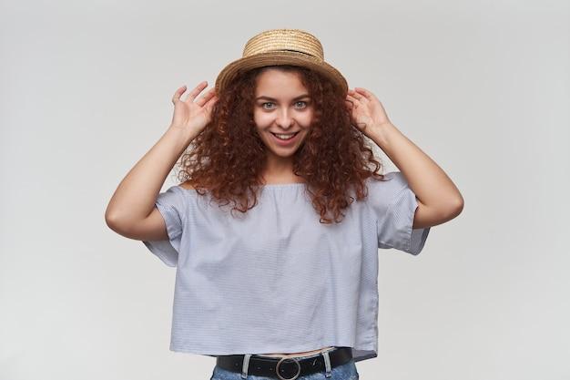 Retrato de uma garota ruiva atraente e adulta com cabelo encaracolado. usando blusa listrada de ombros largos e chapéu. tocando em seu chapéu e sorrindo. isolado sobre a parede branca