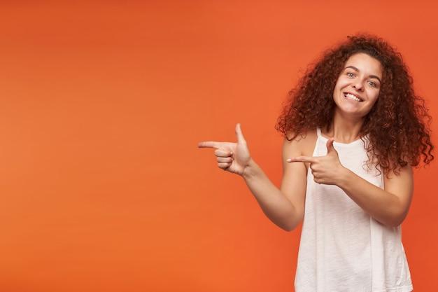 Retrato de uma garota ruiva atraente e adulta com cabelo encaracolado. usando uma blusa branca sem ombros. apontando para a esquerda no espaço da cópia, isolado sobre a parede laranja