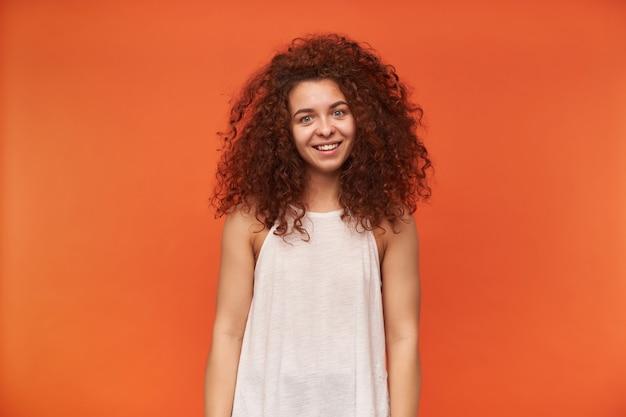Retrato de uma garota ruiva atraente e adulta com cabelo encaracolado. usando uma blusa branca sem ombros. ter cabelos bagunçados e sorrir. isolado sobre a parede laranja