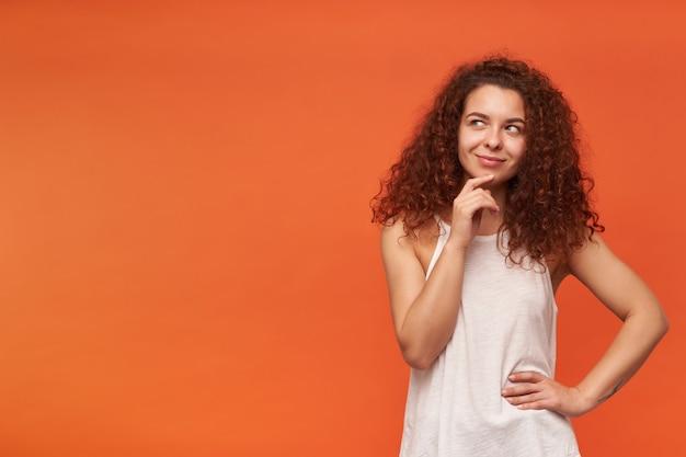Retrato de uma garota ruiva atraente e adulta com cabelo encaracolado. usando uma blusa branca sem ombros. tocando seu queixo e sorrindo, pergunto. observando à esquerda no espaço da cópia, isolado sobre a parede laranja