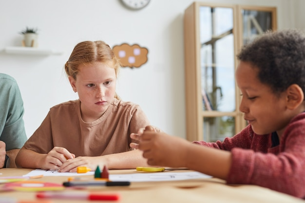 Retrato de uma garota ruiva sardenta olhando para um amigo enquanto desenham juntos durante a aula de arte na escola