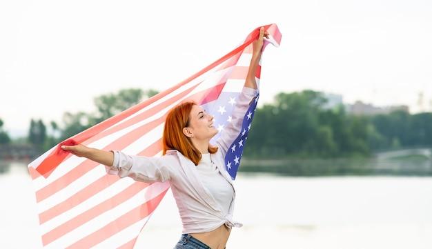 Retrato de uma garota ruiva sorridente feliz segurando a bandeira nacional dos eua nas mãos. mulher jovem positiva comemorando o dia da independência dos estados unidos.