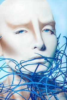 Retrato de uma garota sexy com arte corporal branca na superfície azul