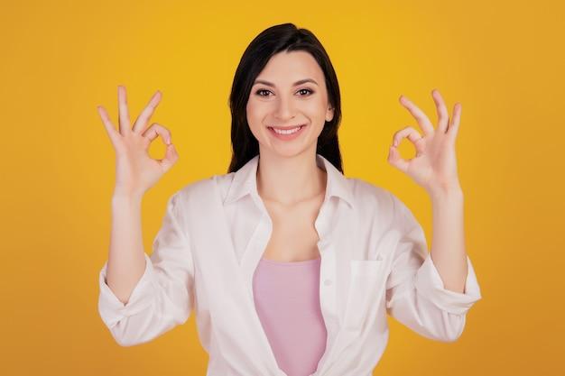 Retrato de uma garota simpática e charmosa levantando as duas mãos e mostrando sinais de ok sobre fundo amarelo
