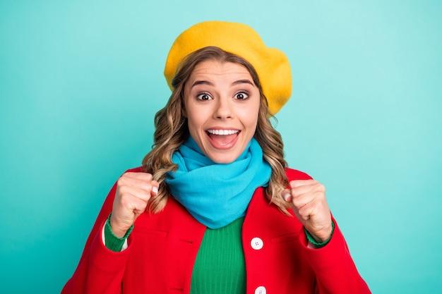 Retrato de uma garota surpresa e positiva impressionada na temporada de venda de loteria de inverno, levantar os punhos gritar divirta-se, use um macacão verde isolado sobre o fundo da cor azul-petróleo