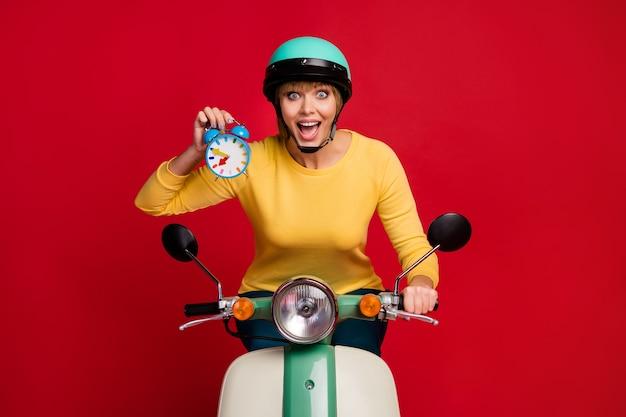 Retrato de uma garota surpresa motorista andando de moto segurando o relógio na parede vermelha