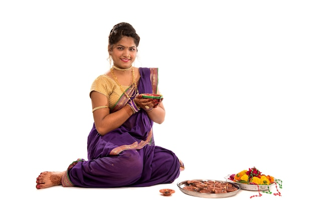 Retrato de uma garota tradicional indiana segurando diya