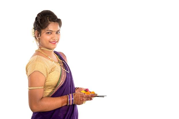 Retrato de uma garota tradicional indiana segurando pooja thali com diya