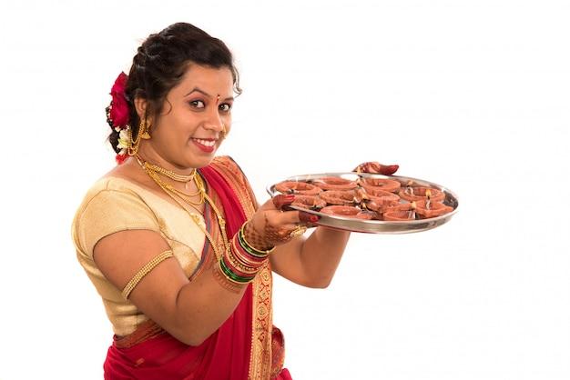 Retrato de uma garota tradicional indiana segurando uma foto de diya, diwali ou deepavali com mãos femininas segurando uma lâmpada a óleo durante o festival de luz no espaço em branco