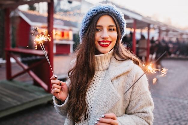 Retrato de uma graciosa mulher de cabelos castanhos em um elegante casaco branco segurando luzes de bengala. foto ao ar livre de uma romântica garota europeia com boina azul posando com estrelinhas na cidade blur