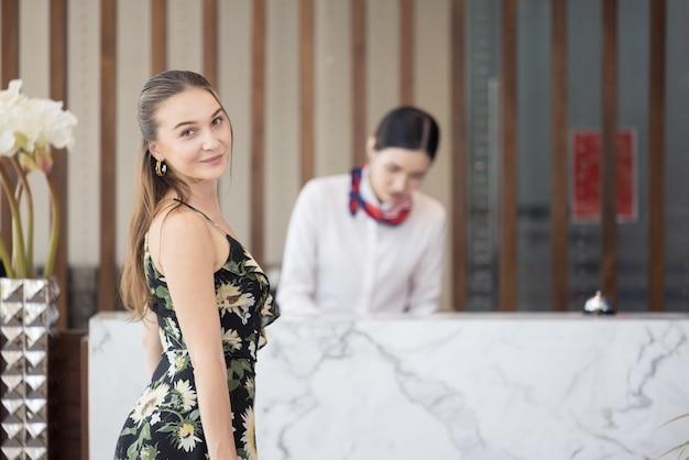 Retrato de uma hóspede com bagagem esperando para fazer o check-in no hotel, conceito de estilo de vida de viagem feliz