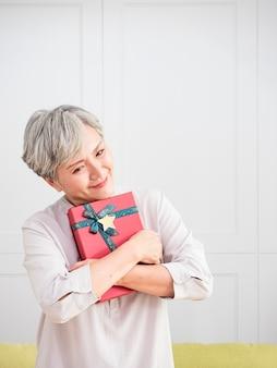Retrato de uma idosa mulher asiática abraço a caixa de presente em casa.