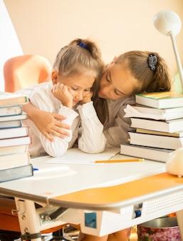 Retrato de uma irmã mais velha abraçando uma irmã mais nova muito chateada que tinha problemas na escola