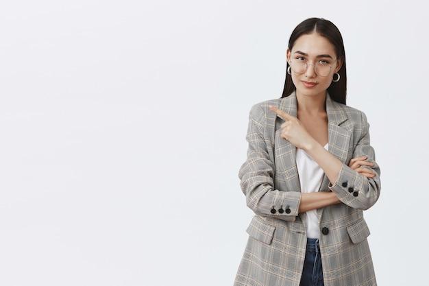 Retrato de uma jornalista bonita e intrigada de óculos e paletó sobre camiseta, apontando para a esquerda e olhando com curiosidade, com alguma intenção interessante