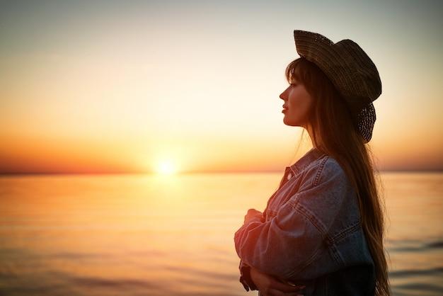 Retrato de uma jovem à beira-mar com um chapéu ao pôr do sol no verão