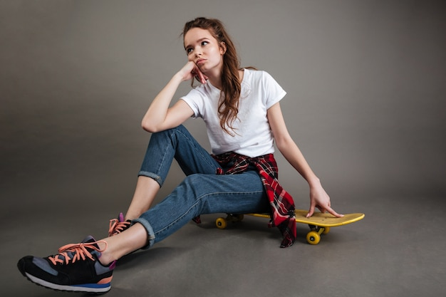 Retrato de uma jovem adolescente sentado no skate