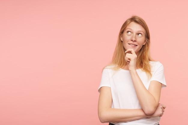 Retrato de uma jovem adorável com cabelo loiro solto mordendo o lábio e olhando positivamente para cima enquanto sonha com algo, posando sobre um fundo rosa