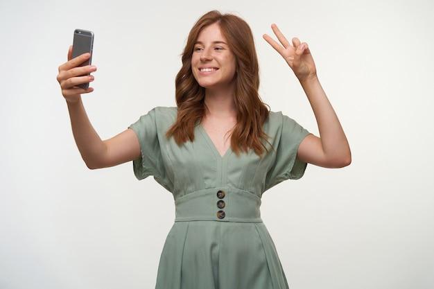 Retrato de uma jovem adorável com sorriso largo e penteado romântico em pé, fazendo selfie no celular, mostrando um gesto de paz