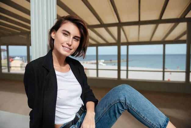 Retrato de uma jovem adorável e alegre sentada no terraço na praia