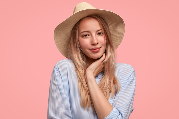 Retrato de uma jovem adorável e atraente usa um chapéu e uma camisa elegantes, segura a mão sob o queixo, mostra sua beleza natural, fica de pé contra a parede rosa
