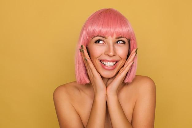 Retrato de uma jovem adorável e feliz senhora de cabelo rosa com maquiagem natural, mostrando seus dentes brancos perfeitos enquanto sorri amplamente, apoiando o queixo nas mãos levantadas enquanto posa sobre a parede de mostarda