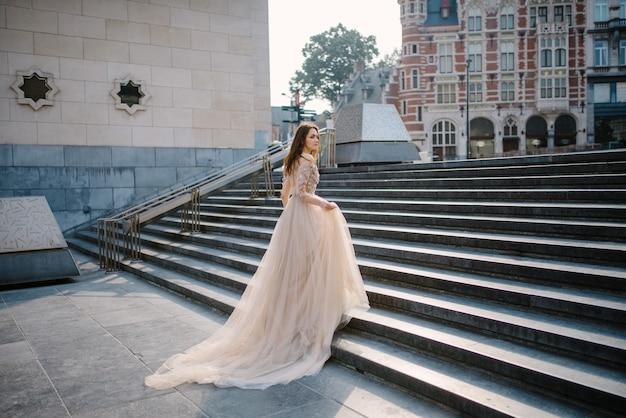 Retrato de uma jovem adorável em um vestido exuberante andando pelo parque e o grande palácio (bruxelas)