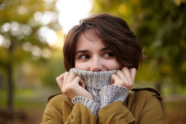 Retrato de uma jovem adorável mulher de cabelos castanhos com penteado casual congelando após uma longa caminhada e escondendo o rosto em um poloneck aconchegante e aconchegante enquanto fica em pé sobre árvores amareladas