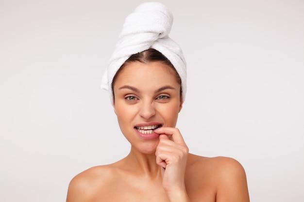 Retrato de uma jovem adorável mulher de cabelos escuros com uma toalha na cabeça, franzindo a testa e mordendo o dedo enquanto olha para a câmera, posando sobre um fundo branco com ombros nus