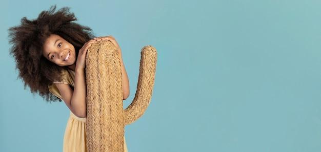 Retrato de uma jovem adorável posando com um cacto falso