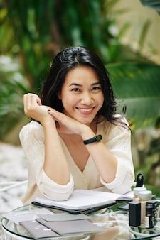 Retrato de uma jovem adorável sentada ao ar livre à mesa com catálogos e potes de cosméticos