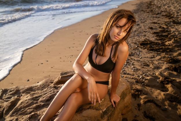 Retrato de uma jovem adulta em um maiô na praia, uma modelo loira com cabelo comprido está sentado ...