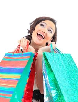 Retrato de uma jovem adulta feliz, com sacos codificados por cores.