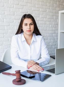 Retrato de uma jovem advogada em seu local de trabalho com laptop e martelo