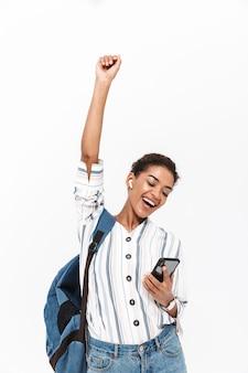 Retrato de uma jovem africana atraente carregando uma mochila em pé, isolada na parede branca, ouvindo música com fones de ouvido sem fio, segurando o telefone celular, comemorando