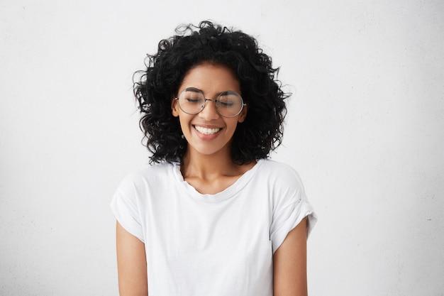 Retrato de uma jovem africana carismática e charmosa com cabelos cacheados, usando óculos sylish, sorrindo amplamente, estreitando os olhos