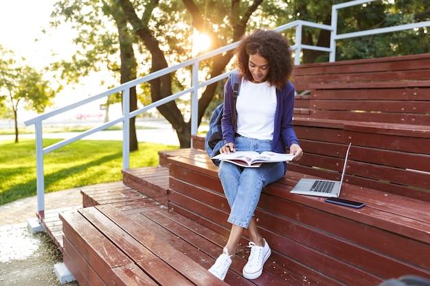 Retrato de uma jovem africana sorridente com uma mochila descansando no parque, lendo uma revista.