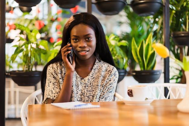 Retrato de uma jovem africana sorridente, sentada em um café, fazendo uma ligação