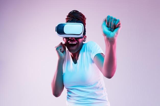 Retrato de uma jovem afro-americana brincando com óculos vr em luz de néon em fundo gradiente