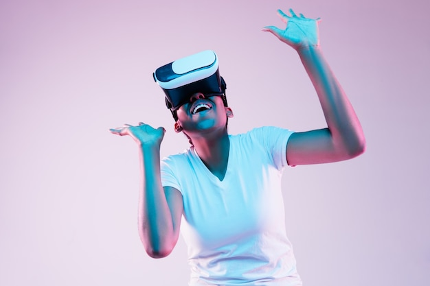Retrato de uma jovem afro-americana brincando com óculos vr em luz de néon em gradiente
