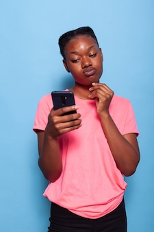 Retrato de uma jovem afro-americana conversando com um amigo usando o smartphone