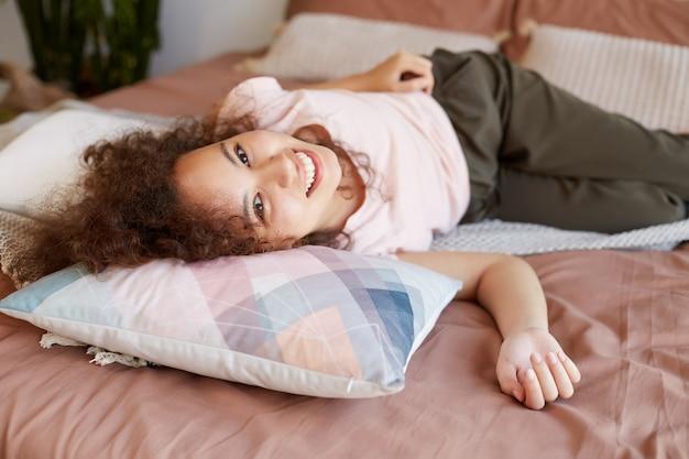 Retrato de uma jovem afro-americana deitada na cama, sorrindo e parece feliz, aproveite o dia ensolarado em casa.
